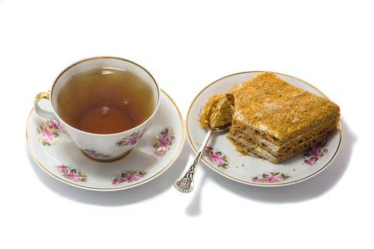 cup of tea with cake on plate, isolated on white