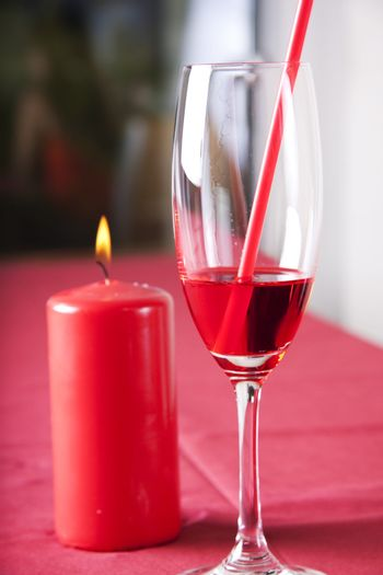 Red cocktail and candle