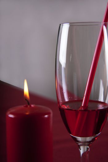 Red cocktail and a red candle