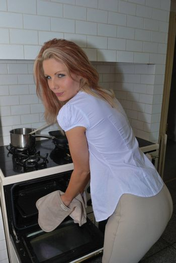 Pretty girl getting roast from the oven