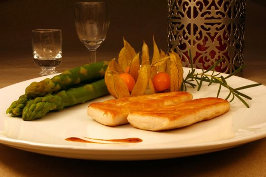 Light dish of grilled chicken with asparagus, physalis and rosemary