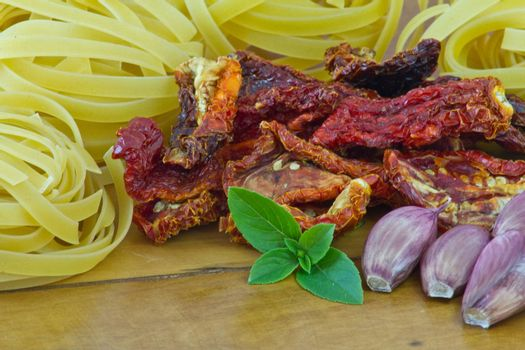 Ingredients to make a italian food, including pasta, garlic, dry tomato, basil and rosemary.