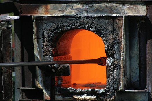 Glass-blower gets preparation from the furnace.
