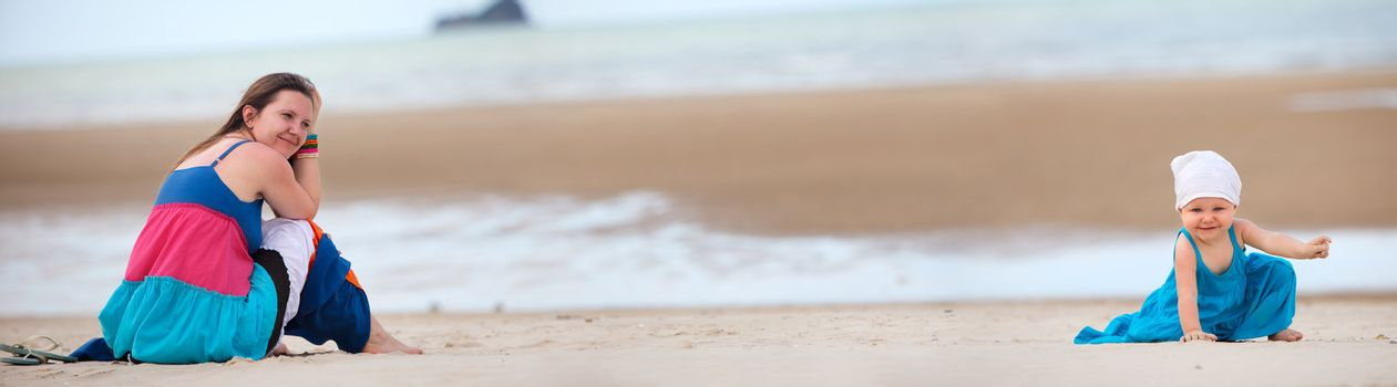 Panoramic photo of young mother and baby girl on the beach