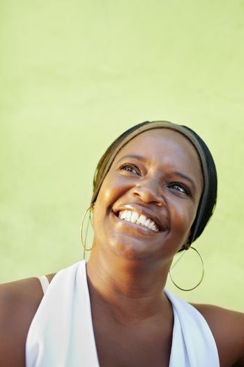 portrait of happy african adult woman looking up and smiling. Vertical shape, copy space