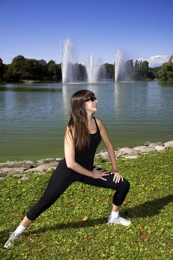 Woman stretching by the lake