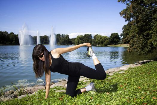 Woman stretching in front of a lake