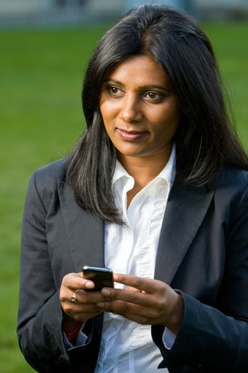 Pretty indian girl using mobile or handphone for communication