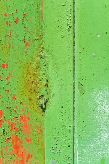 Close up shot of a metal door with green peeling paint