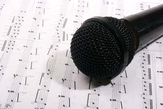 Black microphone and music (note) book.