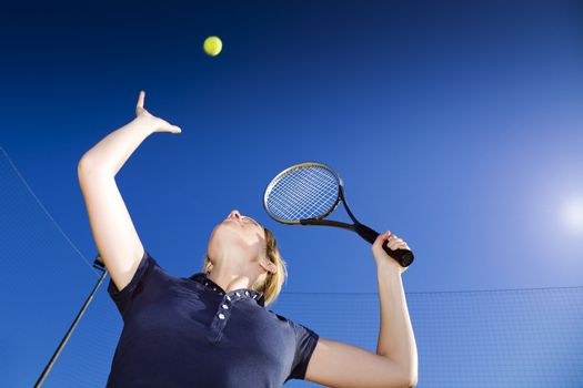blond woman playing tennis, about to hit the ball. Copy space