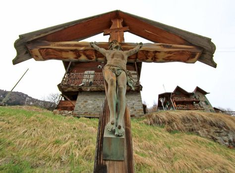 Brown wood cross with Jesus sculpture on it in front of chalet jouses in the mountain