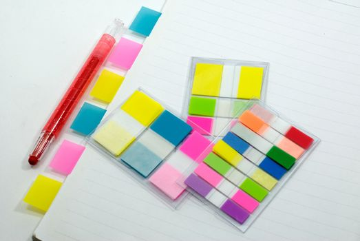 Here are a lot of tags on notebook with pen in white background.