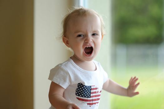 Little baby is shouting loudly wearing united states flag shirt