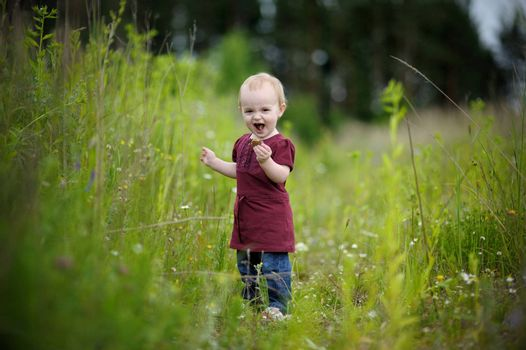 Happy little baby wearing nice dress in a meadow eating cookie
