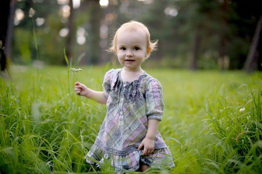 Smiling little baby girl wearing nice dress in a meadow