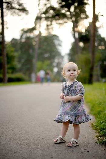 Little baby girl wearing nice dress on the park alley