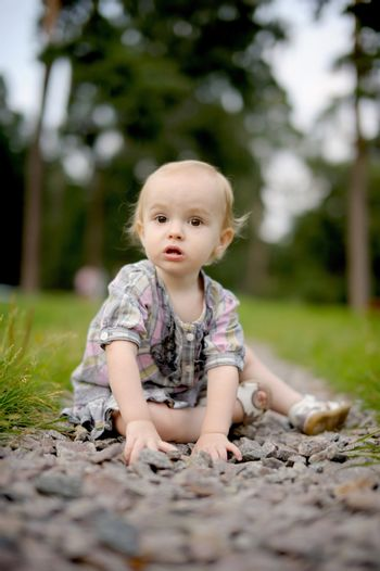 Sad little baby girl sitting on the alley of stones