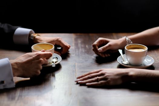 Bride's and groom's hands and coffee cups on the table
