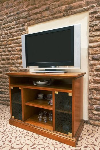 The modern TV on a background of a stone wall