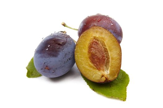 Whole plum and halves isolated on the white background