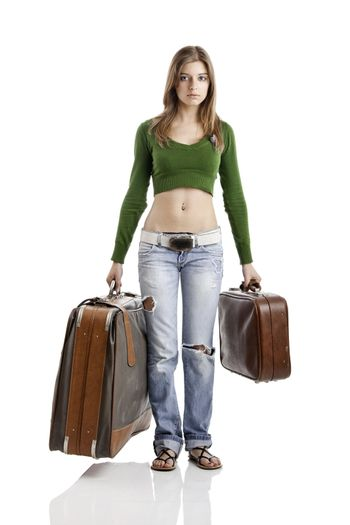 Beautiful young woman holding two old leather suitcases