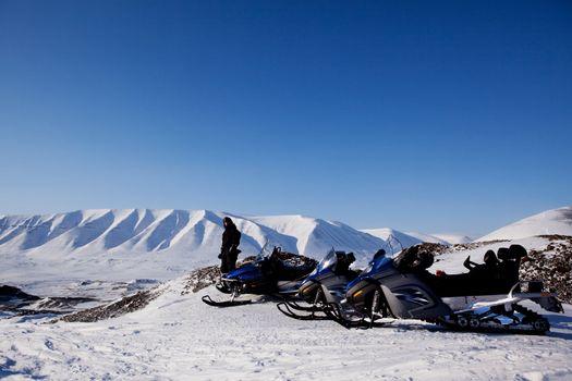Snowmobiles in a barren winter landscape, Svalbard, Norway
