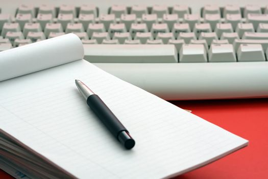 Stack of paper and keyboard, symbolizes communication