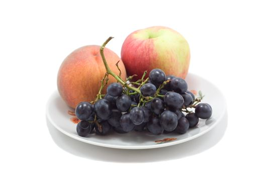 plate with fruits, peach, apple and grapes, isolated on white