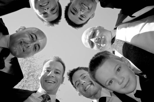A groom and his groomsmen posing together in a huddle formation.