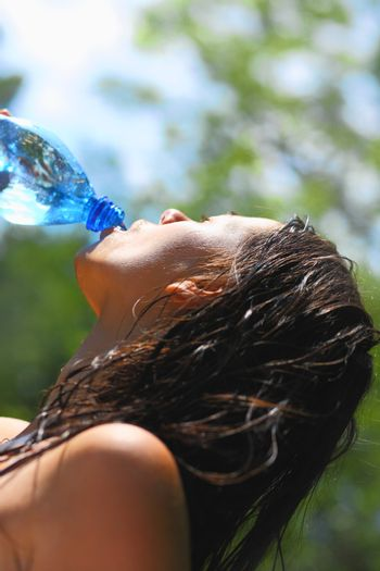 Young woman drinking water outdoors. She has a thirst.  Side view