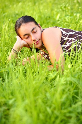 Young woman resting in green meadow