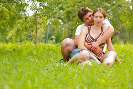 Young attractive couple sitting on a grass in a meadow