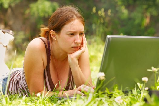 Young woman using her laptop outdoors.