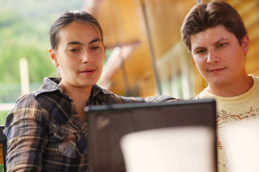 Close-up of man and woman  working on laptop.