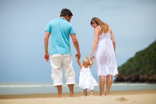 Young family of three on tropical beach.