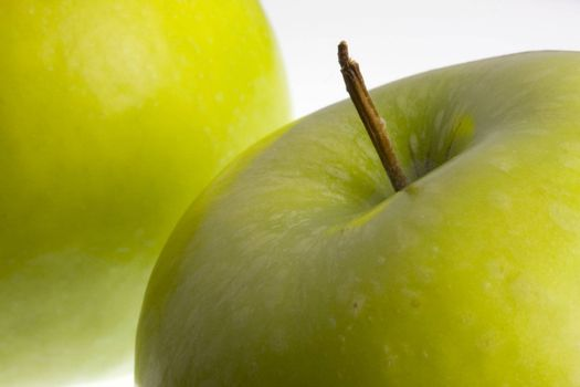 macro of two green Granny Smith apples on white background, selective focus