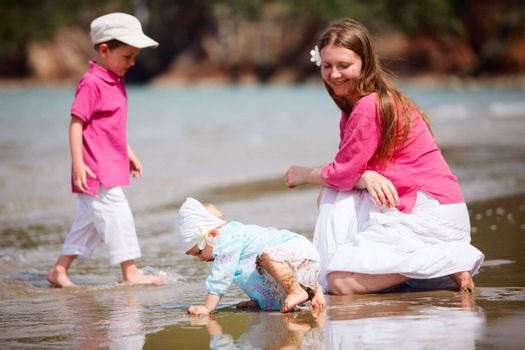 Young mother with two kids at the beach