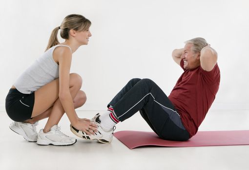 young personal trainer and senior adult exercising in gym