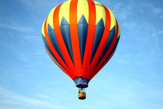 Hot air balloon on light blue background with red blue and yellow highlights.