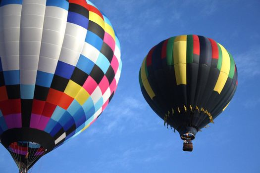 Pair of hot air balloons flying accross a blue sky