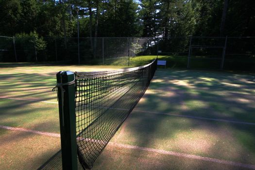 View of a tennis net on grass court as sun sets
