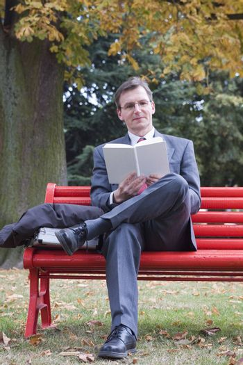 Businessman reading a book on a red bench in a park