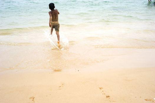 Hikkaduwa, Sri Lanka - February 04, 2011: Sri Lankan boy running on the beach to the ocean.