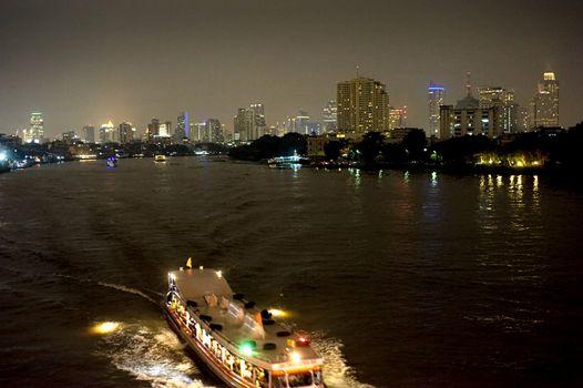 Boat at night on the Chao Phraya River in Bangkok, Thailand.