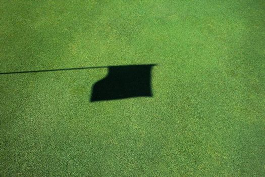 Shadow of flag on top of pin on a golf green