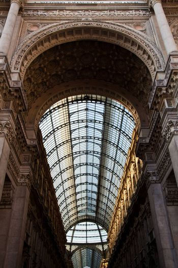 The Galleria Vittorio Emanuele II is a covered double arcade formed of two glass-vaulted arcades at right angles intersecting in an octagon, prominently sited on the northern side of the Piazza del Duomo in Milan.