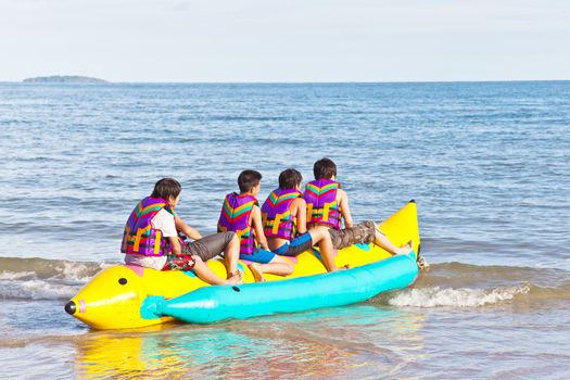 group of young people riding banana boat