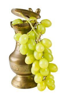 A copper pot with grapes