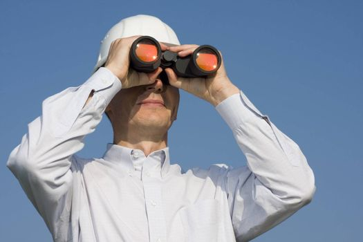Engineer with white hardhat looking through binocular